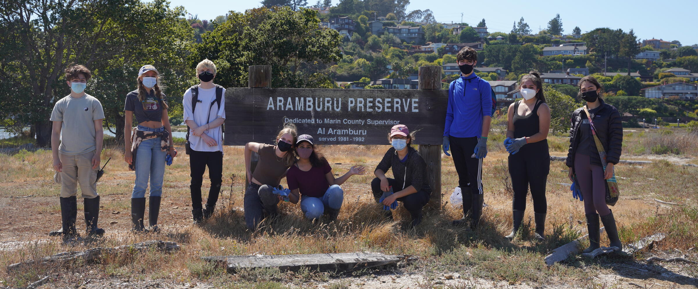 Volunteers Standing at Aramburu Island Sign